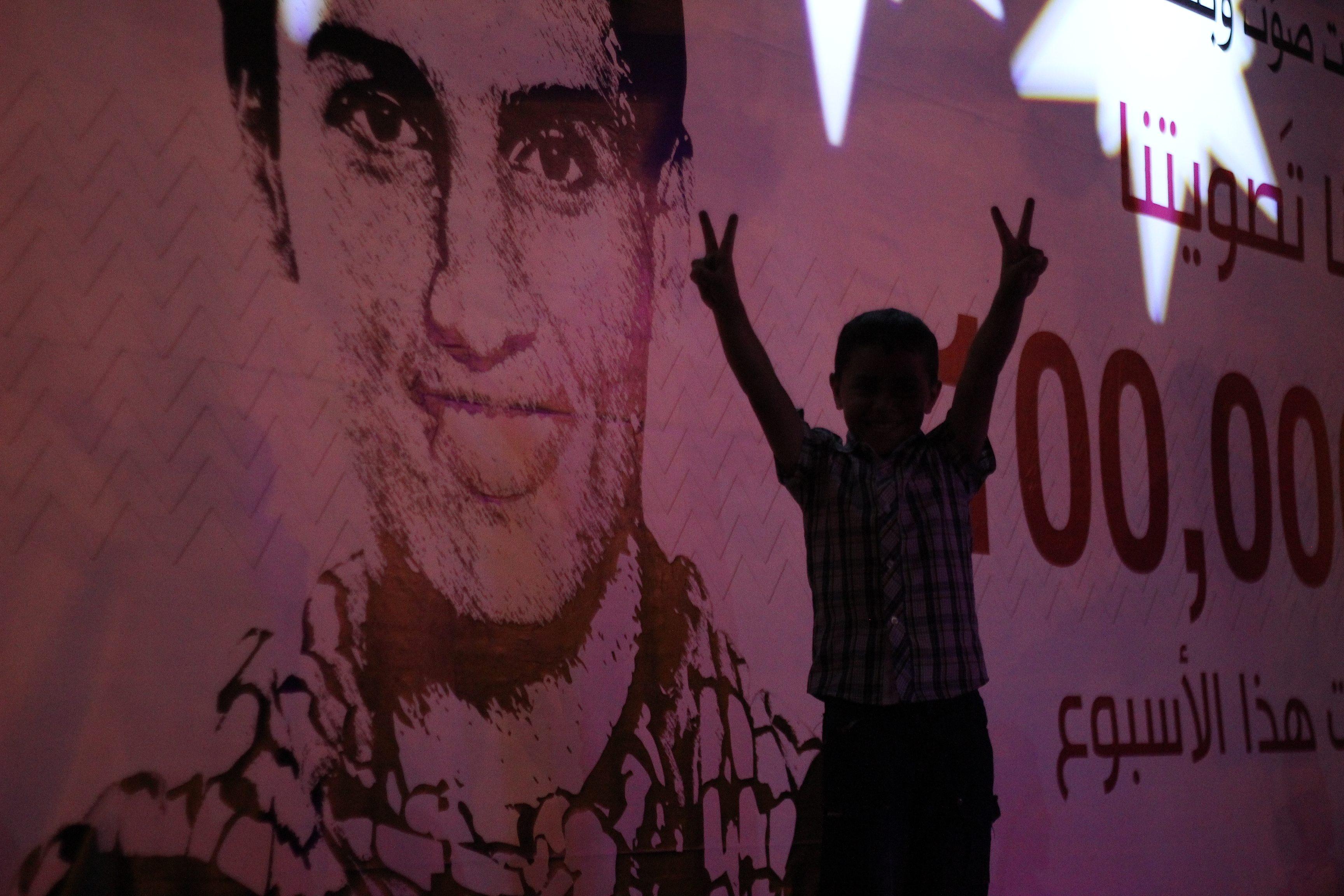 Un jeune Palestinien fait le signe de la victoire devant un poster de Mohammed Assaf à Ramallah le soir de la finale d'Arab Idol www.merblanche.com all rights reserved