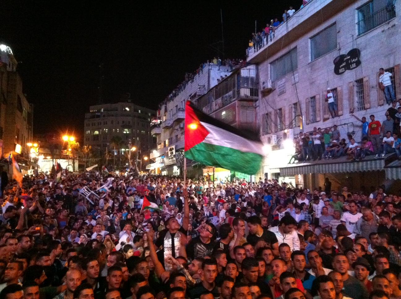 Un drapeau palestinien fièrement brandi au-dessus de la foule à Ramallah le soir de la finale d'Arab Idol www.merblanche.com all rights reserved