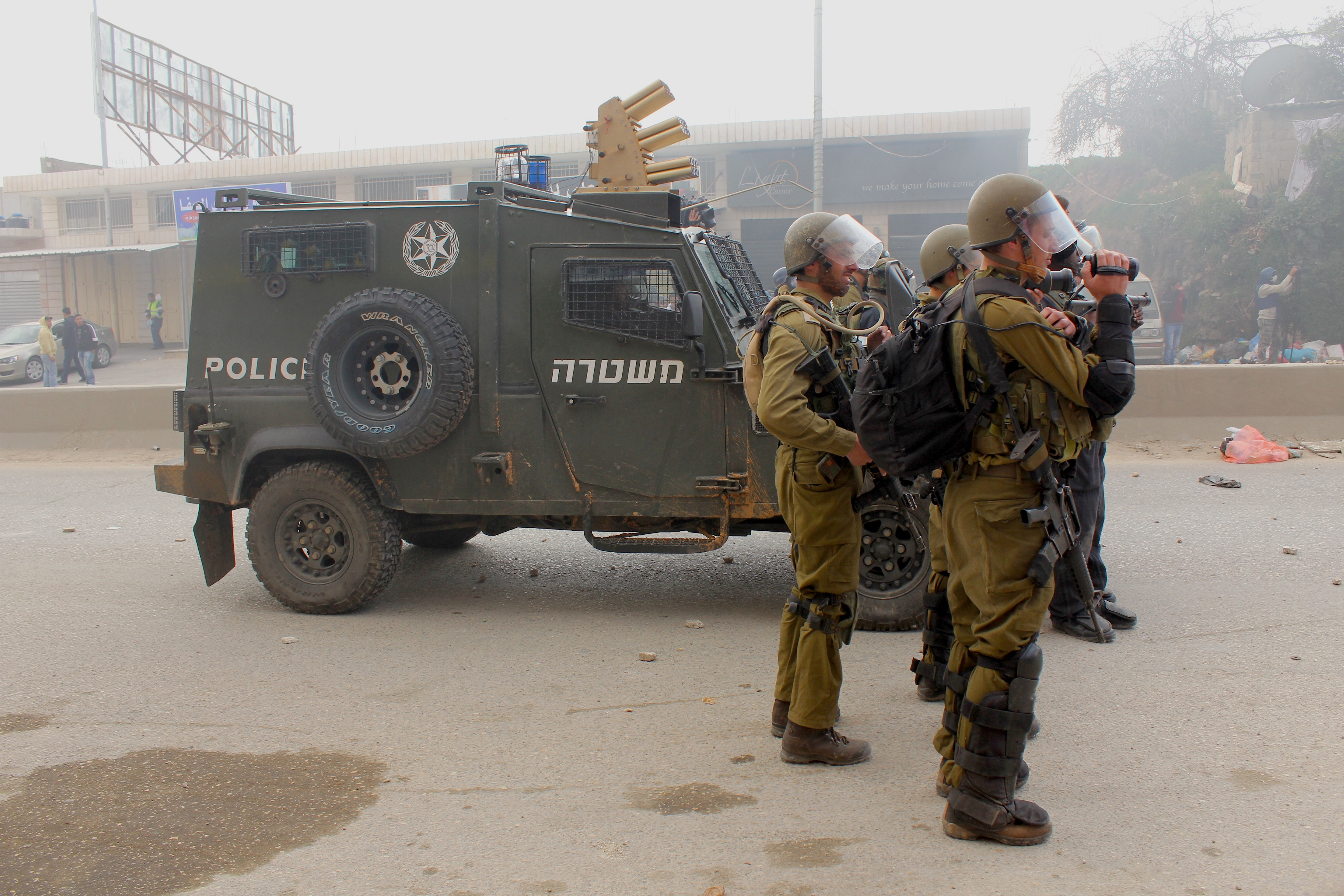 Des soldats israéliens lançant des gaz lacrymogènes sur les manifestants palestiniens. Qalandia checkpoint, mars 2011 www.merblanche.com all rights reserved